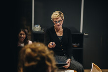 Female CEO Giving Instructions In Meeting.