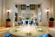 Fountain In The Lobby Of The Regent Hotel In Tivat, Montenegro. Decorative Fountain Bowl For Indoor Use With Sofa For Relaxation And Long Corridor.