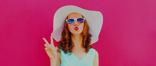 Portrait Close Up Of Beautiful Young Woman Blowing Her Red Lips Sending Sweet Air Kiss Wearing A Summer Straw Hat On A Pink Background