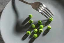 Some Green Peas And A Fork With Shadows On A Gray Plate, Meager Diet Meal After The Resolution To Slim Down, Copy Space, Selected Focus