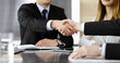 Unknown businessmen shaking hands above the glass desk in a modern office, close-up. Unknown business people at meeting. Teamwork, partnership and handshake concept