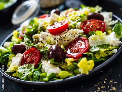Fototapeta Fresh Greek salad - feta cheese, tomatoes, cucumber, lettuce, black olives and onion on wooden table obraz