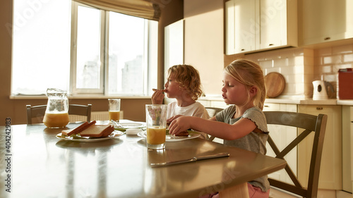 Two cute little kids eating toasted bread with chocolate butter for breakfast or Fotobehang