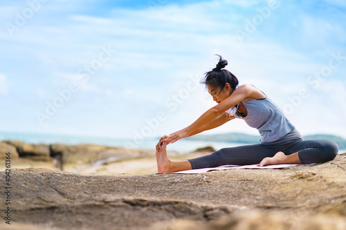 Photo A beautiful woman doing yoga on the rocks at the beachside.