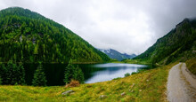 Mountain Lake With Green Mountains And Trees Near A Dirt Road Panorama