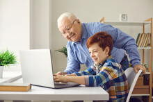Senior People Embracing Modern Technology While Children Are Learning Online: Happy Smiling Grandfather Asks Grandson To Teach Him To Use Laptop Computer Or Helps Little Boy With Home Assignment