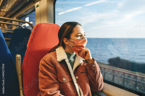 Obraz Girl in a protective face mask on the train. Travel by train or suburban trip. - fototapety do salonu