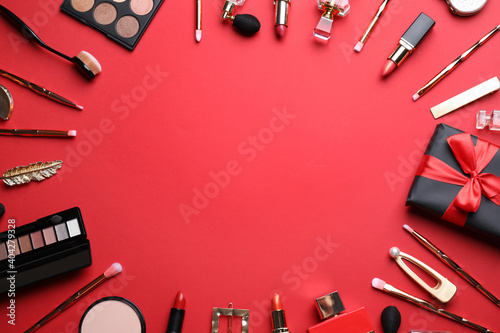 Fotografie, Obraz Makeup brushes and cosmetic products on red background, flat lay
