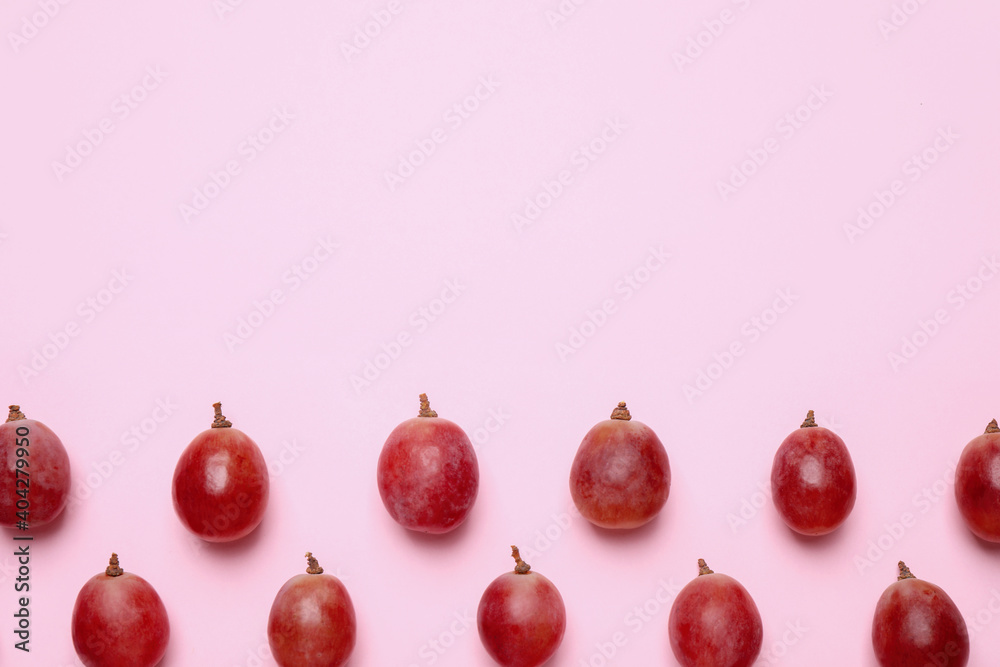 Fototapeta Flat lay composition with fresh ripe grapes on pink background. Space for text