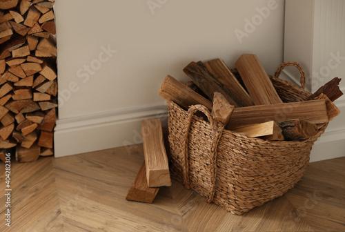 Slika na platnu Basket with firewood on floor in room
