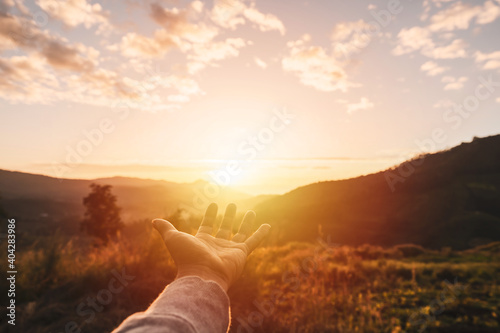 Young man hand reaching for the mountains during sunset and beautiful landscape Fototapeta