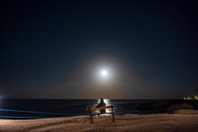Woman Sits On A Bench And Looks At The Rising Moon Over The Sea At Night
