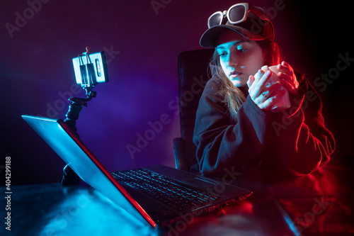 Obraz Blogger woman next to a laptop. Girl holds a cup of tea in her hands. She records video on her smartphone. Blogger woman broadcasts video. Woman student with laptop in a dark room. Online streaming - fototapety do salonu