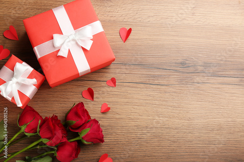 Gift boxes, roses and paper hearts on wooden background, flat lay with space for text. Valentine's Day celebration