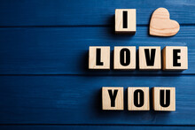 Cubes With Words I Love You And Heart On Blue Wooden Background, Flat Lay. Space For Text