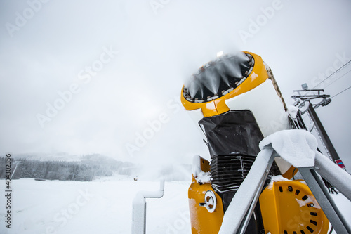 Snow cannon, machine or gun snowing the slopes or mountain for skiers ans snowbo Wallpaper Mural