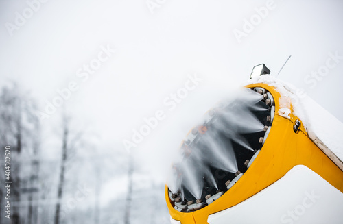 Snow cannon, machine or gun snowing the slopes or mountain for skiers ans snowbo Fotobehang