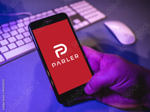 Man watching app Parler on his smartphone in front of a mouse and keyboard - popular social network