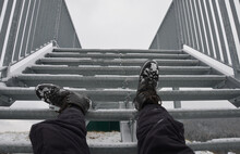 The Tourist View From With Metal Stairs Glides Dangerously In The Winter. Hiker In Hiking Boots Fell From The Skin And Lying Injured On The Stairs. Legs Broken With Bruises Danger Of Falling Down.
