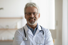 Head Shot Portrait Of Smiling Older Male General Practitioner In Eyeglasses And Medical Coat Posing In Clinic. Happy Sincere Trusted Middle Aged Doctor Looking At Camera, Medical Service Concept.