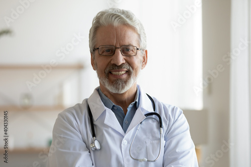 Obraz Head shot portrait of smiling older male general practitioner in eyeglasses and medical coat posing in clinic. Happy sincere trusted middle aged doctor looking at camera, medical service concept. - fototapety do salonu