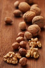 Walnuts And Hazelnuts. Still Life From Whole Nuts And Kernels On Brown Textured Wooden Background. Selective Focus On Kernels