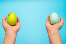 Hands Holding Painted Easter Eggs. Easter Eggs In A Childs Hands On A Blue Background