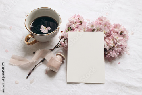 Obraz Wedding stationery mock-up. Blank greeting card and cup of coffee. White linen tablecloth background. Pink blossoming cherry tree branches and ribbon. Feminine still life composition. Flat lay,top. - fototapety do salonu