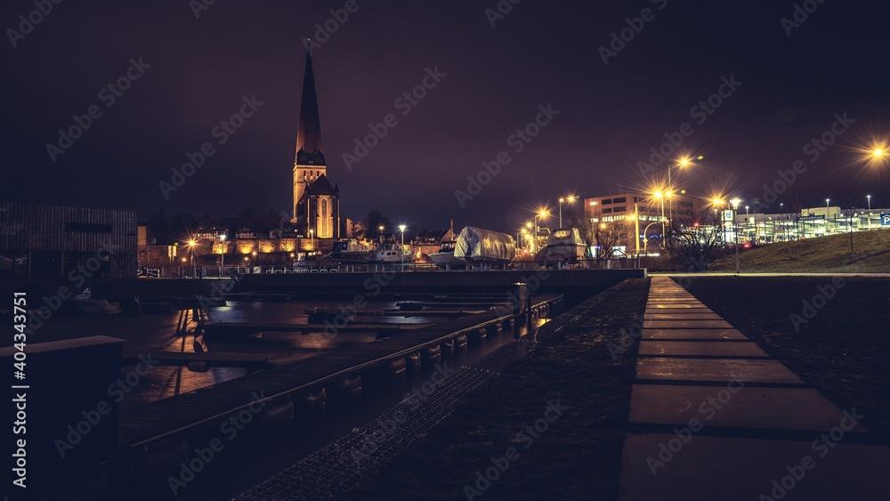 Fototapeta Illuminated City By River Against Sky At Night