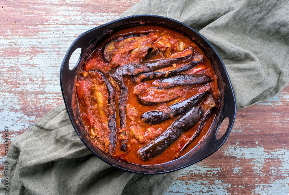 Fototapeta Modern style slow cooked Persian lamb eggplant stew khoresh bademjan served as close-up in a Design pot on a wooden board with copy space