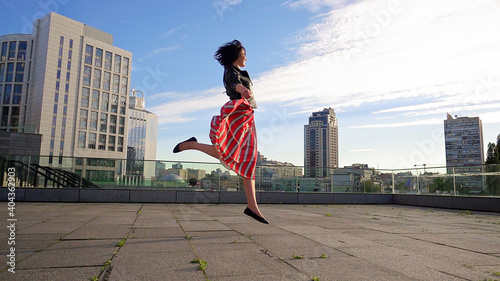 Fotografie, Obraz Happy Woman Wearing Striped Skirt And Jacket On Footpath In City