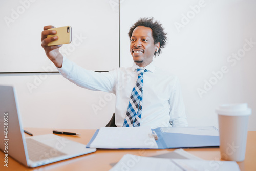 Fototapeta Businessman taking selfie with phone at office.