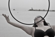 Woman With Plastic Hoop Dancing At Beach