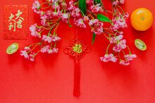 Hanging Pendant For Chinese New Year Ornament (word Means Wealth) With Red Envelope Packet Or Ang Bao (word Means Auspice), Gold Ingots, Orange And Chinese Blossom Flowers On Red Background.