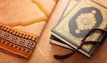High Angle View Of Koran And Prayer Beads On Table