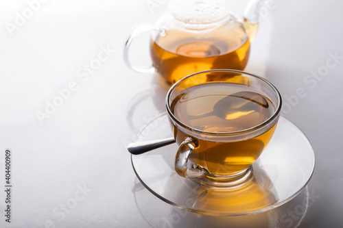 Canvas a cup of freshly brewed hot tea in a glass and a teapot on the white table