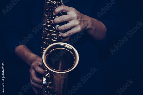Obraz na plátně Close up of a young musician  man hands hold and playing  saxophone on black background with copy space