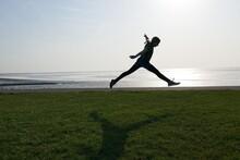 Full Length Of Girl Jumping At Beach Against Sky