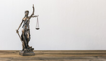 Close-up Of Lady Justice On Table Against Wall