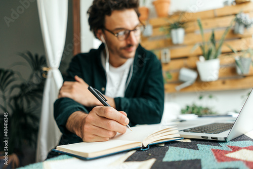 Obraz Man with laptop working remotely from home. Freelancer at remote work. Cozy workplace - fototapety do salonu