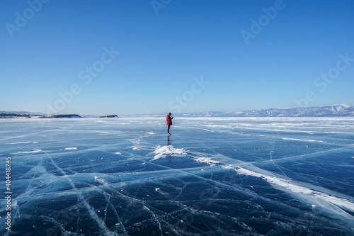 man in winter jacket travel holding camera tripod on frozen Baikal lake in Irkutsk, russia in early February