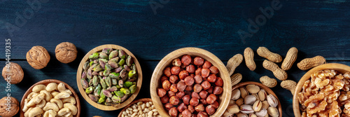 Fototapeta Nuts panorama with copy space. A variety of nuts, shot from the top on a dark blue wooden background obraz