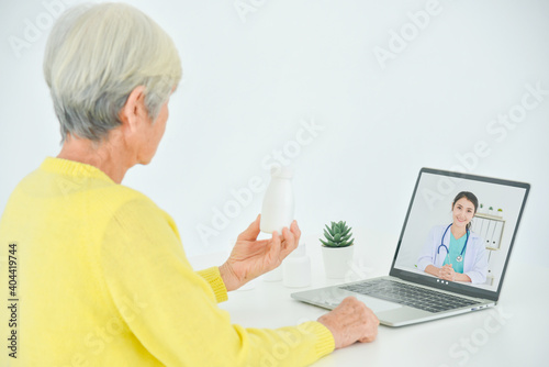 Fotografija Senior woman sitting in front of laptop computer making video call chat with doctor