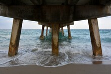 Scenic View Of Sea Against Sky From Beneath A Fishing Pier