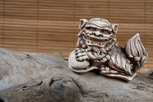 Closeup Of Japanese Netsuke Figure On Wooden And Bamboo Background. Statue Lion Mascot