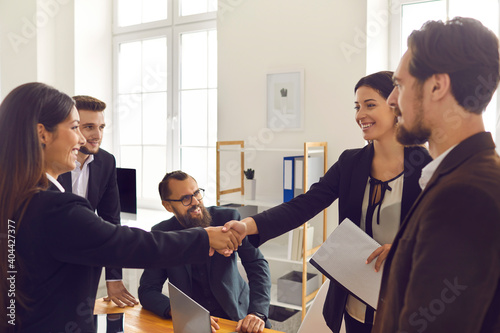 Canvas Print Happy business people closing deal and shaking hands after negotiation meeting i