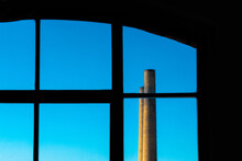 Low Angle View Of Blue Sky With Smoke Stack Seen Through Window