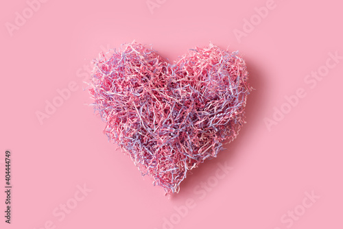 Foto Shape of pink heart like tangle of packaging material, greeting card on pink bac