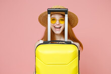 Traveler Tourist Smiling Hapy Ginger Woman 20s In Straw Hat Glasses Hiding With Suitcase Valise Isolated On Pastel Pink Background Passenger Travel Abroad Weekends Getaway Air Flight Journey Concept.