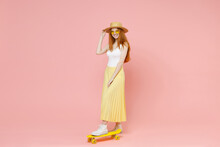 Full Length Body Young Smiling Redhead Energetic Ginger Teenager Pretty Caucasian Woman 20s In Glasses Summer Clothes Maxi Skirt Stand On Skateboard Isolated On Pastel Pink Background Studio Portrait.
